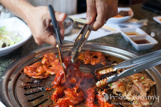 cutting meat over the grill at Taegukgi Korean BBQ